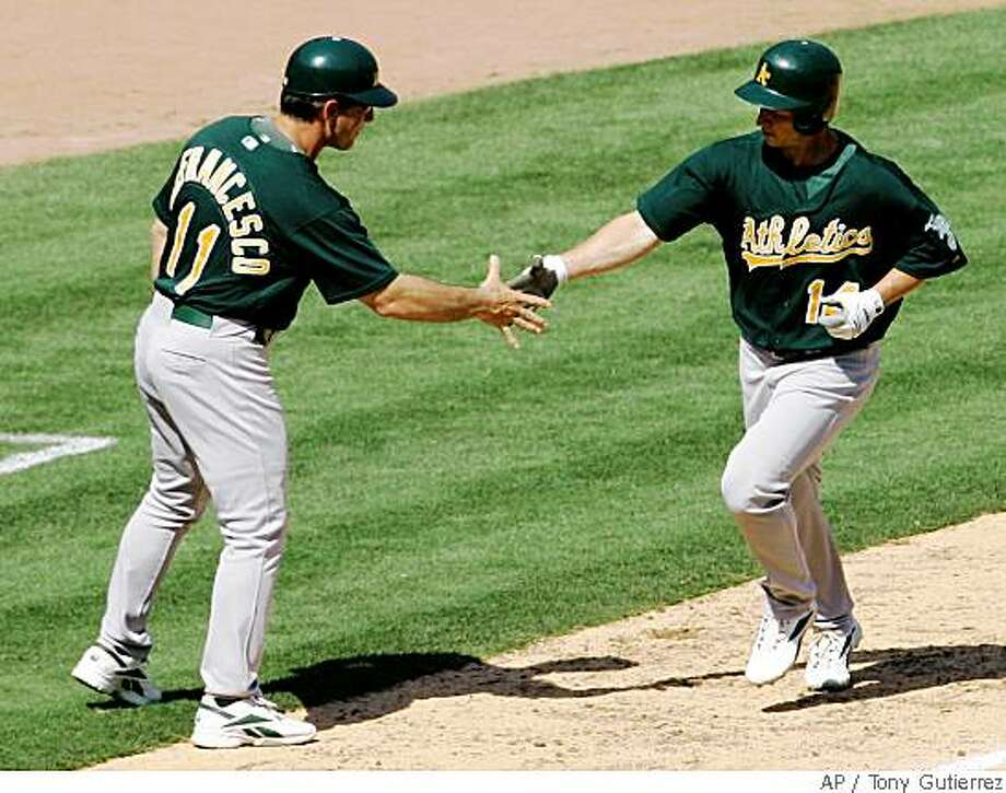 Oakland Athletics third base coach Tony Defrancesco (11) congratulates Mark Ellis, right, on his solo home run in the seventh inning off a pitch from Texas Rangers' Frank Francisco in a baseball game Sunday, June 1, 2008, in Arlington, Texas. The Athletics won 13-8. (AP Photo/Tony Gutierrez) Photo: Tony Gutierrez, AP
