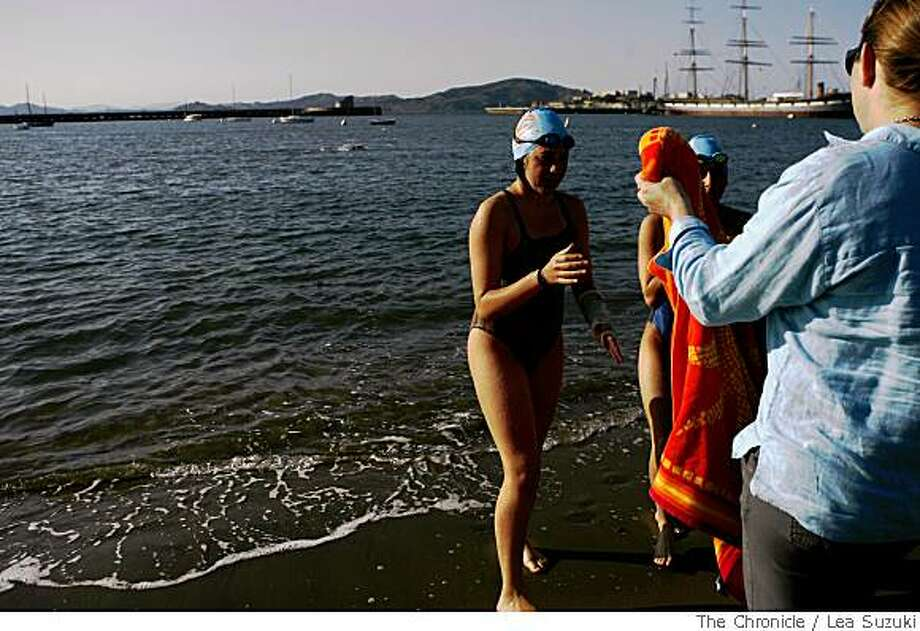 Martha Salomon (right) hands her daughter, Delia Salomon (left),15,and her pacer, Leore Geller (center behind towel), 18, towels as they exit the water after swimming for 47 minutes at Aquatic Park on Wednesday April 30, 2008. Salomon who dreams of swimming the English Channel will make the attempt in August after she turns 16.Photo By Lea Suzuki/ San Francisco Chronicle Photo: Lea Suzuki, The Chronicle