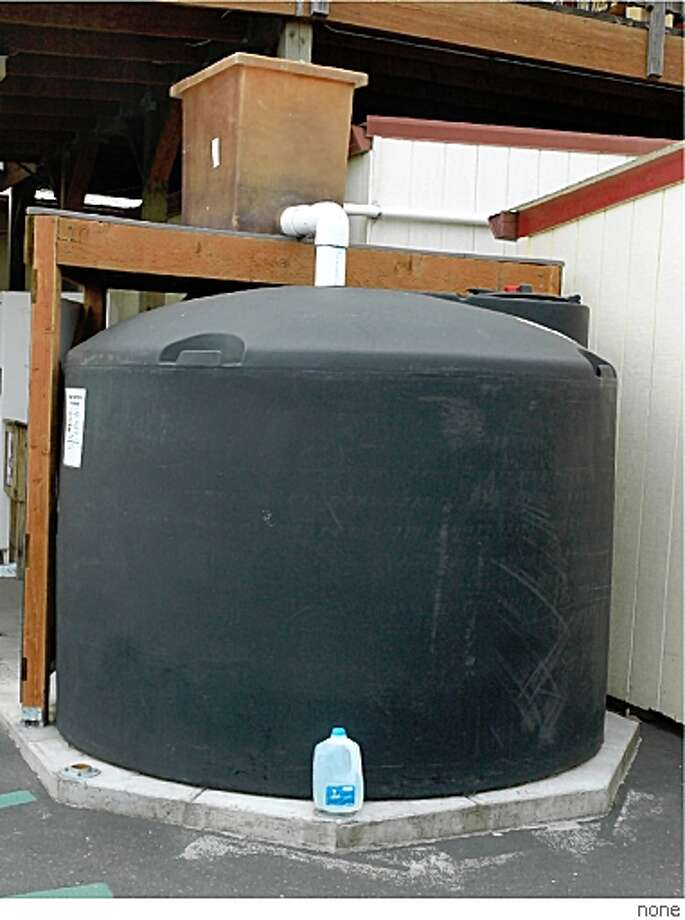 A one-gallon water jug sits in front of a 1,500 gallon rainwater catchment system at a natural foods coop in Corvallis, Oregon. The first-flush washer/filter sits on its own wooden support system. The dark color inhibits algae growth in the tank. Note the cleanout hatch and the white inflow pipe behind the tank that brings water from a distant roof. Photo: None