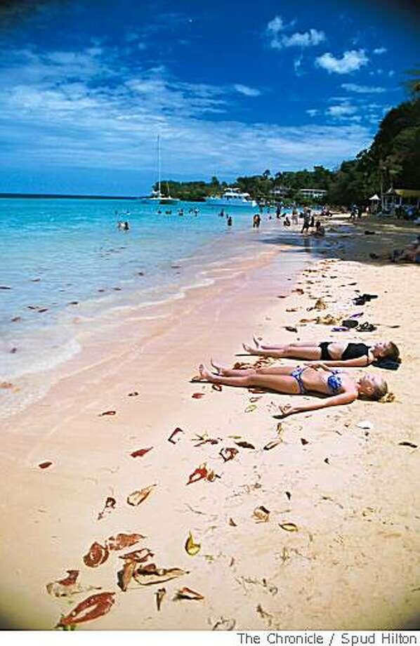 TRAVEL CARIBBEAN -- Sunbathers enjoy a beach near Ocho Rios, Jamaica, a popular port among Caribbean tourists and cruise ships. Photo: Spud Hilton, The Chronicle