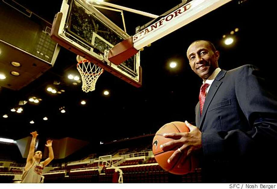Stanford men?s basketball coach Johnny Dawkins poses at Maples Pavillion on Friday, May 23, 2008, in Stanford, Calif. In the background, one of Dawkin?s players practices free throws.Photo by Noah Berger / Special to the Chronicle Photo: Noah Berger, SFC