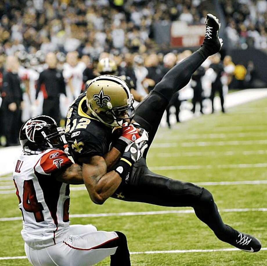 New Orleans Saints wide receiver Marques Colston (12) catches a touchdown pass in front of Atlanta Falcons cornerback Tye Hill (24) in the first half of an NFL football game in New Orleans, Monday, Nov. 2, 2009. (AP Photo/Bill Feig) Photo: Bill Feig, AP