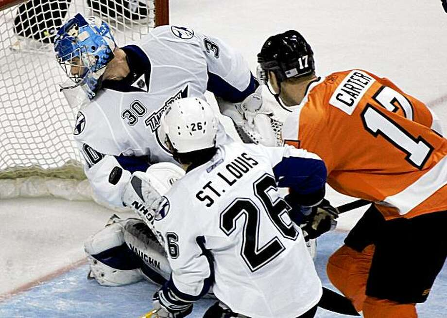 Philadelphia Flyers center Jeff Carter, right, scores a power play goal past Tampa Bay Lightning goalie Antero Niittymaki, of Finland, as Tampa Bay Lightning's  Martin St. Louis, left, looks on in the third period of a NHL  hockey game Monday, Nov. 2, 2009, in Philadelphia. The Flyers won 6-2. (AP Photo/Tom Mihalek) Photo: Tom Mihalek, AP