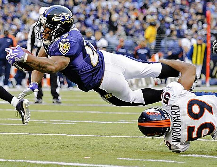 Baltimore Ravens running back Ray Rice, top, leaps into the end zone for a touchdown as Denver Broncos linebacker Wesley Woodyard (59) tries to hang on  during the fourth quarter of an NFL football game, Sunday, Nov. 1, 2009, in Baltimore. The Ravens won 30-7. (AP Photo/Nick Wass) Photo: Nick Wass, AP