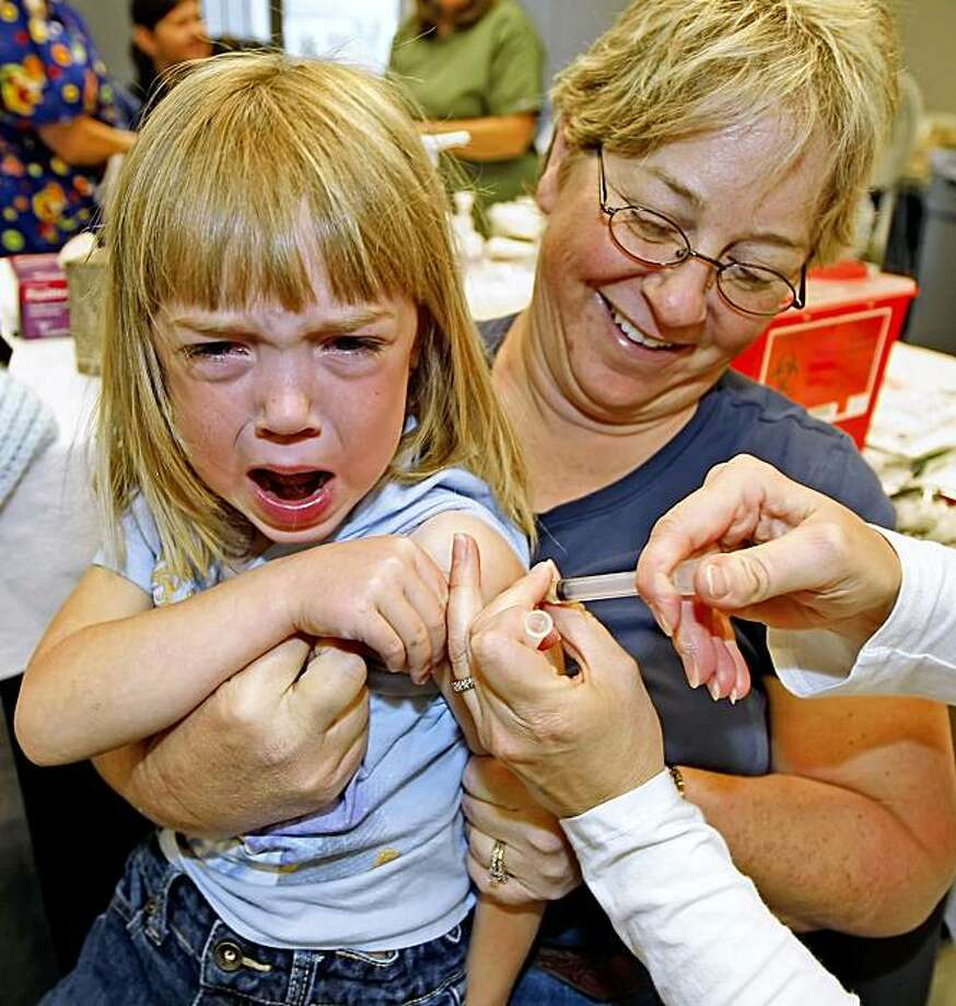 PROVO, UTAH - OCTOBER 27:  A nurse gives a shot of the H1N1 vaccine to Casie Chatwin (L) as her mom Valerie (R) holds her at the Utah County Health Department October 27, 2009 in Provo, Utah. After health department got a shipment of 4000 vaccines overnight, a large line formed with a wait of four to five hours. (Photo by George Frey/Getty Images) Photo: George Frey, Getty Images