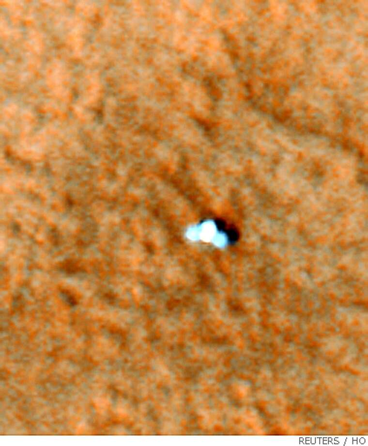 NASA's Mars Phoenix Lander can be seen with its solar panels deployed on the Mars surface in this image captured from Nasa's Mars Reconnaissance Orbiter May 27, 2008. The small science probe blazed through the salmon-colored skies of Mars on Sunday, touching down on a frozen desert at the planet's north pole to search for water and assess conditions for sustaining life, NASA officials said. REUTERS/NASA/JPL-Caltech/University of Arizona/Handout.  FOR EDITORIAL USE ONLY. NOT FOR SALE FOR MARKETING OR ADVERTISING CAMPAIGNS. Photo: HO, REUTERS