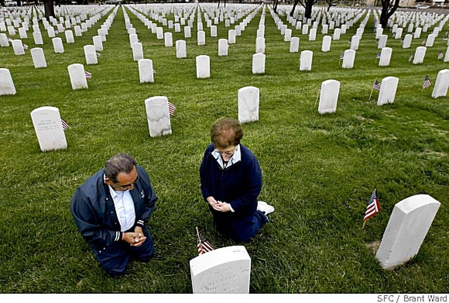 Al Gonzales, left, and his wife Irene stop to pray at headstones after attending the Memorial Day observances at the Golden Gate National Cemetery in San Bruno, Calif., on May 26, 2008. Gonzales, 82, is a Navy veteran from World War II and has  attended every Memorial Day event at the cemetery for the past 32 years.  Photo by Brant Ward / San Francisco Chronicle Photo: Brant Ward, Chronicle