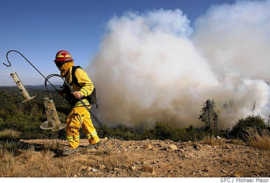 Captain Gerry Laird with San Jose fire removes some bird feeders to a safe place at a home along Summit Rd. as the edge of the Summit fire moves closer, on May 22, 2008, near Corralitos, Calif. in the Santa Cruz Mountains.Photo by  Michael Macor/ San Francisco Chronicle Photo: Michael Macor, SFC