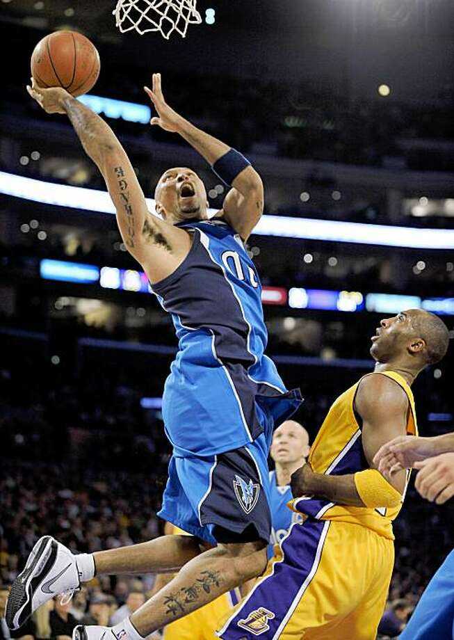 Dallas Mavericks forward Shawn Marion, left, puts up a shot as Los Angeles Lakers guard Kobe Bryant defends during the first half of their NBA basketball game, Friday, Oct. 30, 2009, in Los Angeles.  (AP Photo/Mark J. Terrill) Photo: Mark J. Terrill, AP