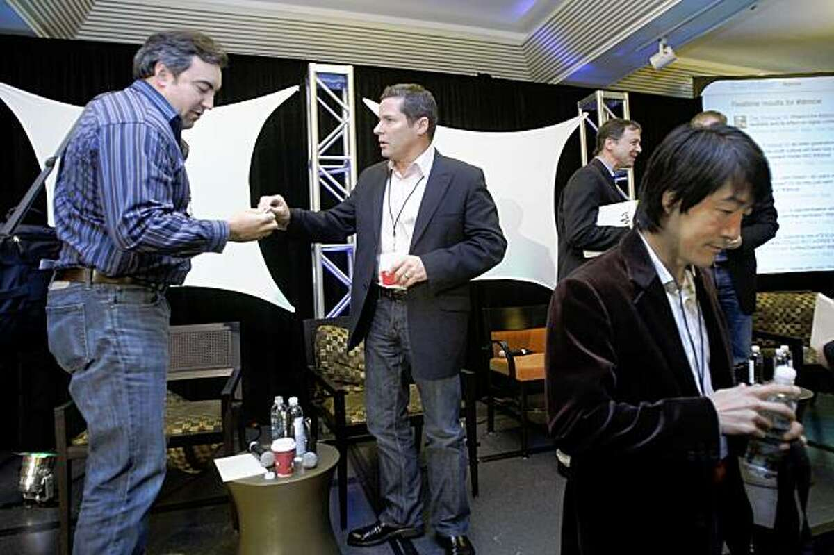 John Welch (left), CEO of Making Fun, exchanging cards with Curt Marvis (middle), president of digital media at Lionsgate, and Daren Tsui (bottom right), CEO of MSpot, at the Digital Media Conference in Hotel Kabuki in San Francisco, Calif., on Wednesday, October 28, 2009.