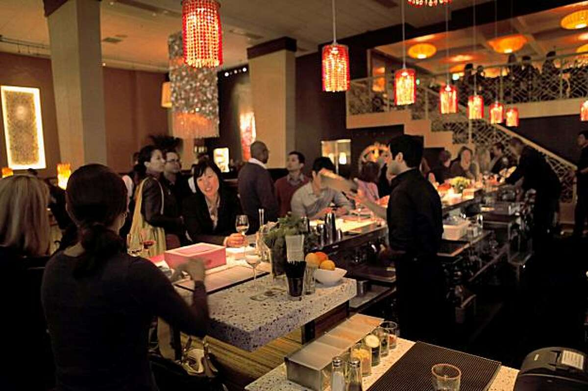 96 Hours Bar Bites feature the scene, people, food and drink at Dosa on Fillmore in San Francisco. This is a restaurant that has a large lounge area to the right and full dining room on the left, separated by a low wall.