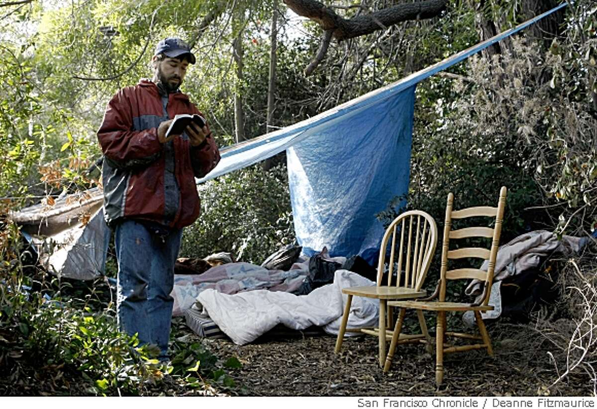 Vincent Pannizzo, 39, reads from the New Testament in his homeless camp near a freeway in Oakland on May 9, 2008. He quit working on his PhD at UC Berkeley to become a street preacher in Oakland, Calif.Photo by Deanne Fitzmaurice / San Francisco Chronicle