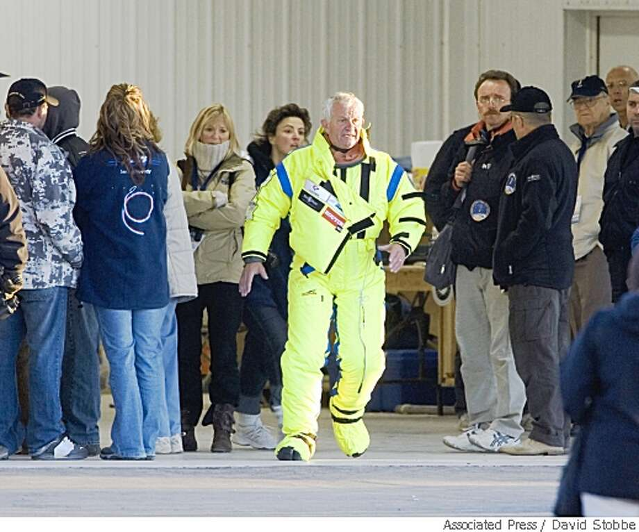 French skydiver Michel Fournier, 64, walks around in an airport hanger with crew members after his second attempt to jump 40 km jump from above the Earth didn't take place Tuesday May 27, 2008, in North Battleford, Saskatchewan. The helium balloon Fournier was going to use to soar to the stratosphere drifted away into the sky without the capsule.  Associated Press photo by David Stobbe Photo: David Stobbe, Associated Press