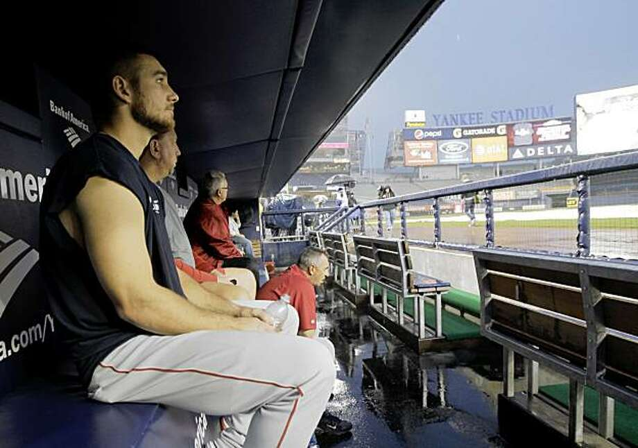 Los Angeles Angels' Jeff Mathis, left, watches the rain from the Angels' dugout with team coaches in Yankee Stadium before Game 6 of the American League Championship baseball series between the New York Yankees and Los Angeles Angels Saturday, Oct. 24, 2009, in New York. Rain threatened to postpone the game. (AP Photo/Kathy Willens) Photo: Kathy Willens, AP