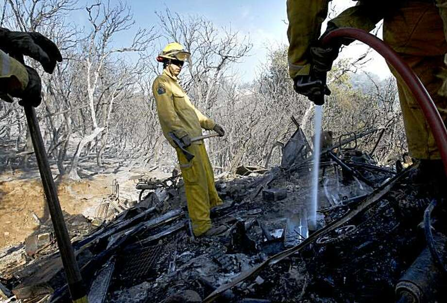 A Cal Fire crew douses hot spots Sunday on the residence and sheds of Joe Waddle, who lives off Summit road. The fire north of Santa Cruz and just off Summit Road, like the infamous Summit fire of a year ago, spooked residents and sent firemen scrambling even after some big October rains. Photo: Brant Ward, The Chronicle