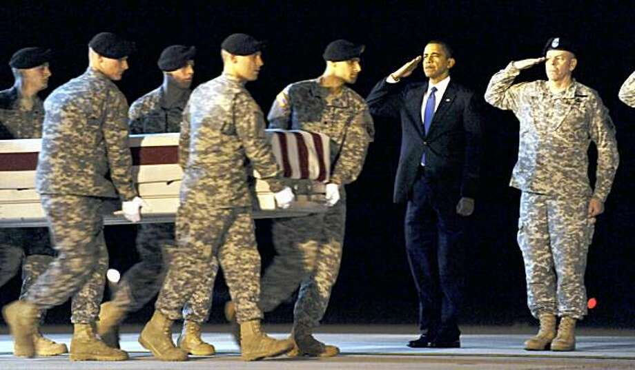 ** ADDS NAME AT RIGHT ** President Barack Obama, second from right, salutes with Maj. Gen. Daniel Wright , right, as a carry team carries the transfer case containing the remains of Army Sgt. Dale R. Griffin of Terre Haute, Ind., who died in Afghanistan according to the Department of Defense, during a dignified transfer at Dover Air Force Base in Dover, Del., Thursday, Oct. 29, 2009. (AP Photo/Susan Walsh) Photo: Susan Walsh, AP