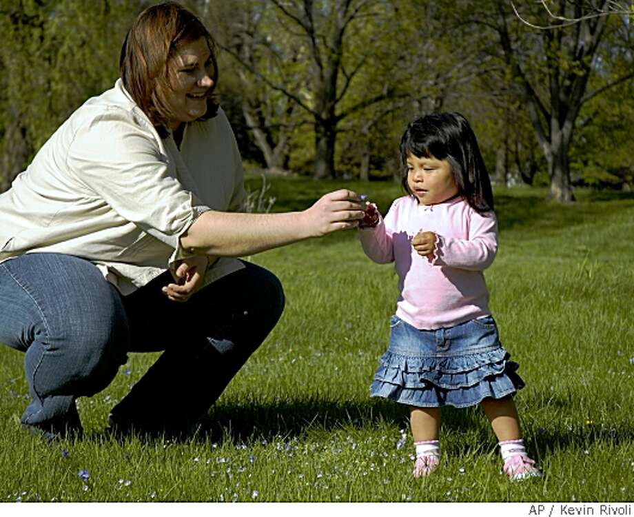 Deborah Surine, a Cornell University employee, picks flowers with her two-year-old daughter Olivia, who was adopted from Guatemala, at their home in Freeville, N.Y., Saturday, May 10, 2008.  Since 2005, about 30 employees at Cornell University have taken advantage of the school's adoption benefits, which include $5,000 in aid per adoption and up to 16 weeks of partially paid leave. (AP Photo/Kevin Rivoli) Photo: Kevin Rivoli, AP