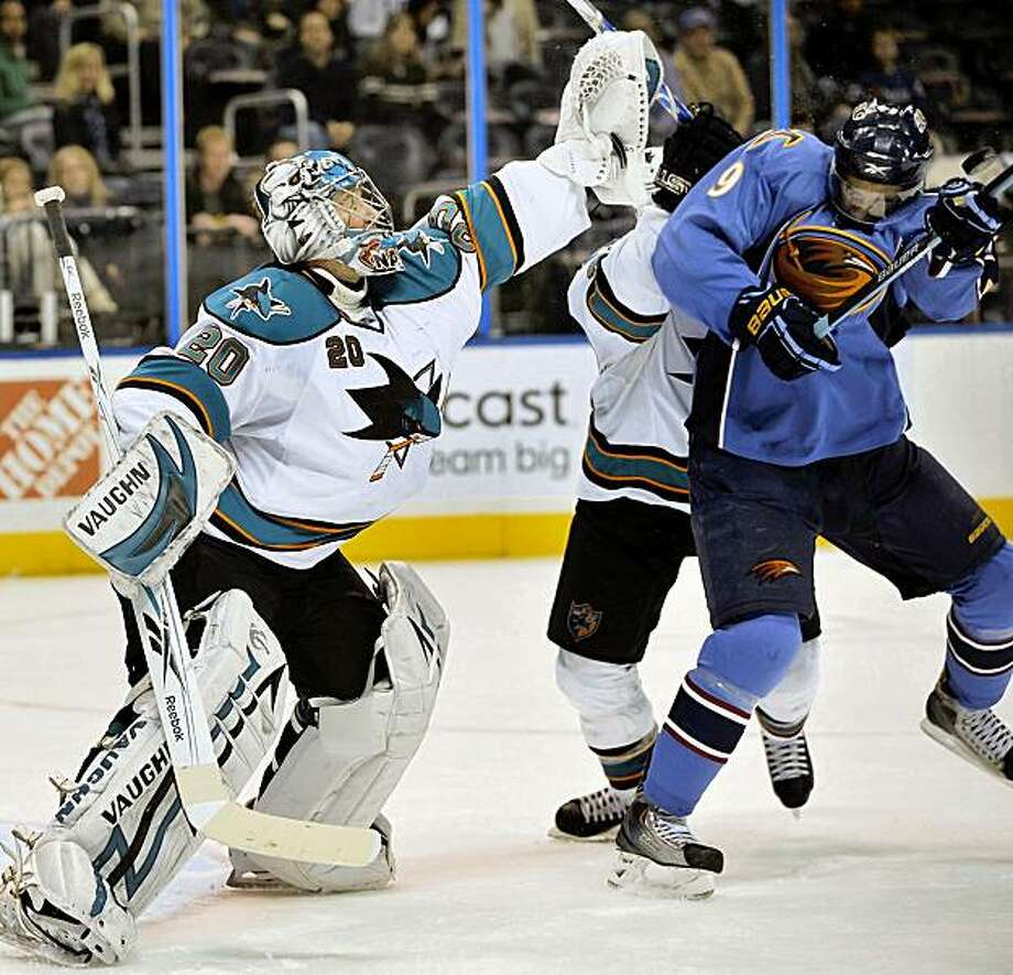 San Jose Sharks goaltender Evgeni Nabokov (20), of Kazakhstan, makes a save as he deflects the puck with Atlanta Thrashers left wing Evander Kane (9) during the third period of an NHL hockey game Saturday, Oct. 24, 2009, at Philips Arena in Atlanta. The Sharks won 4-3. (AP Photo/Gregory Smith) Photo: Gregory Smith, AP