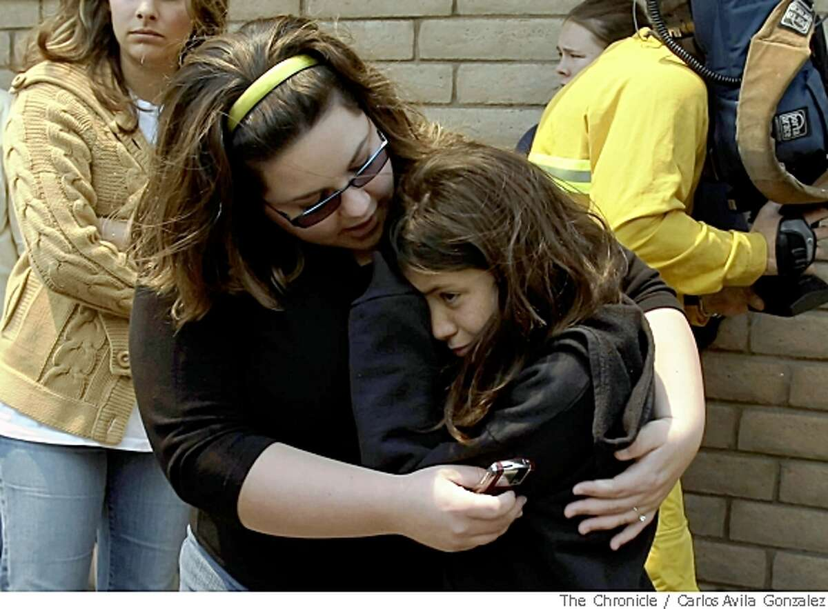 Ashley Picone, left, comforts her sister-in-law, 10-year-old Isabela Cisneros after Isabela's family evacuated their outside Corralitos, Calif., on May 22, 2008. Residents of Corralitos were evacuated as a fast-moving wildfire spread through the Santa Cruz mountains fueled by strong winds.Photo by Carlos Avila Gonzalez / San Francisco Chronicle