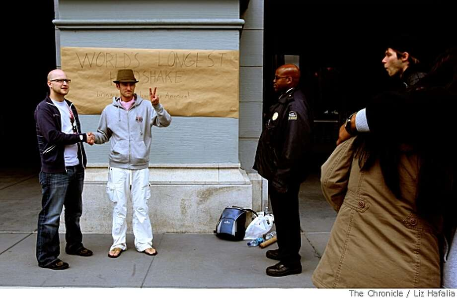 Cory Jens, left, from Muscatine, Iowa and Kevin Whittaker of San Francisco, shake hands in front of the Ferry Building in San Francisco, Calif., as they attempt to break the world record for the longest handshake. The current Guinness World Record for the longest handshake stands at nine hours. Security from the Ferry Building tell them not to display their sign on the property, so Whittaker flashes a peace sign to the guard and viewers before moving across the street.Photo by Liz Hafalia / The Chronicle Photo: Liz Hafalia, Chronicle