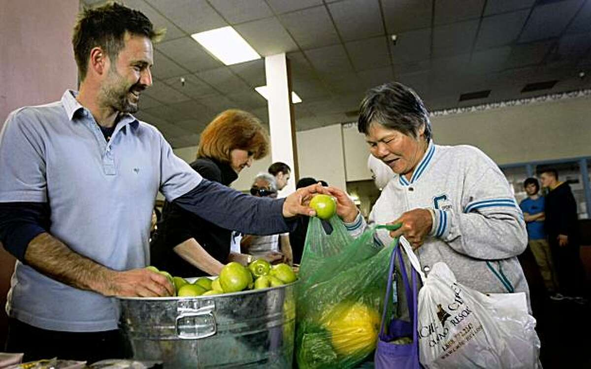 Actor David Arquette passes out apples to Yu Lian Tang during a Tenderloin neighborhood food giveaway at the San Francisco chapter of Youth with a Mission on Ellis Street. Thursday Oct 22, 2009