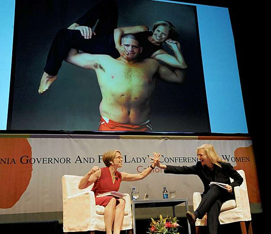 Katie Couric, left, and Annie Leibovitz  high five each other on stage at the Women's Conference on Tuesday, Oct. 27, 2009, in Long Beach, Calif. In background is a portrait of Katie Couric done by Annie Leibovitz.  (AP Photo/Katy Winn) Photo: Katy Winn, AP