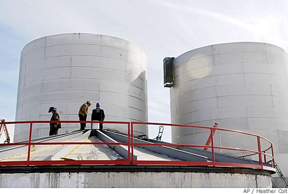 A Feb. 28, 2008 photo shows workers standing atop a grounded roof welding stainless steel fermentation tanks together at the One Earth Energy ethanol plant in Gibson City, Ill. Investors who bought into the ethanol industry not long ago are not seeing the returns they believed were likely. The past couple of months have shaken the industry, with members of Congress urging that an ethanol-production mandate they once approved be rolled back to help blunt rising food prices and shortages overseas. (AP Photo/The News-Gazette, Heather Coit) Photo: Heather Coit, AP