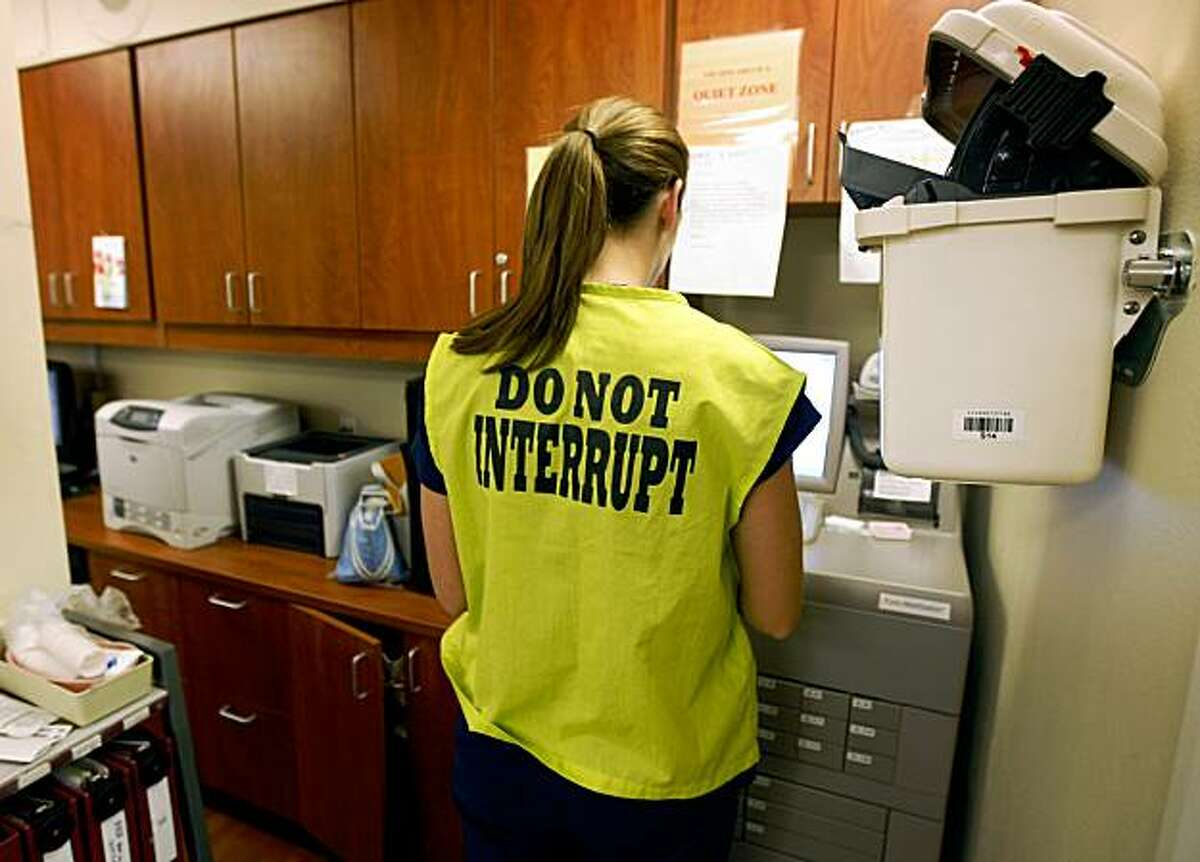 Eleni Drury, a registered nurse in the labor and delivery ward at Saint Rose Hospital, wears a yellow vest to minimize disruptions while dispensing medications in Hayward, Calif., on Tuesday, Oct. 27, 2009.