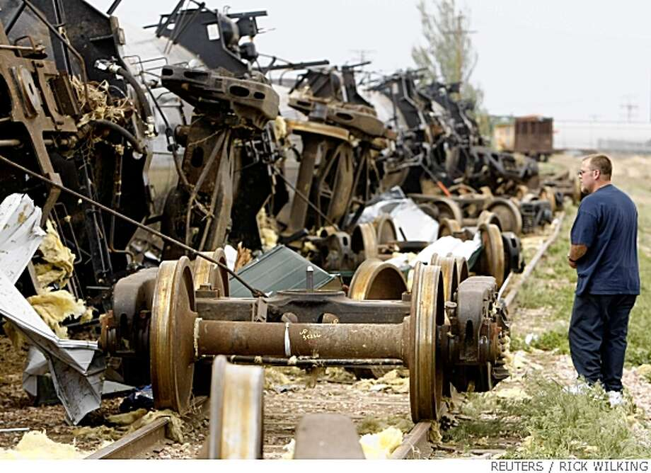 Curtis McFarlane looks at a tanker train blown off its wheels by a tornado in Windsor, Colorado May 22, 2008. Several tornados touched down in the area around lunchtime.  REUTERS/Rick Wilking (UNITED STATES) Photo: RICK WILKING, REUTERS