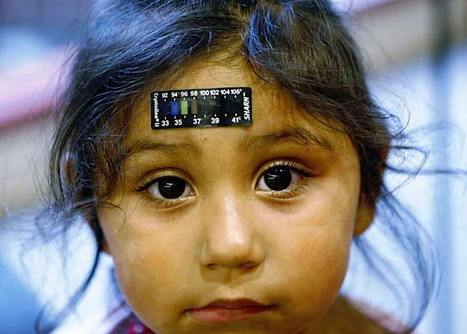 Lucile Packard Children's Hospital at Stanford visitor Sheila Garcia, 3, has her temperature taken on her head before visiting a patient at the hospital in Palo Alto, Calif., Monday, Oct. 19, 2009.  Hospitals around the country are turning away child visitors at the door, restrictions that aim to limit spread of swine flu to patients sick from other causes. But there's no evidence to guide these decisions _ some turn away only the under-12 while others don't welcome teens. (AP Photo/Paul Sakuma) Photo: Paul Sakuma, AP