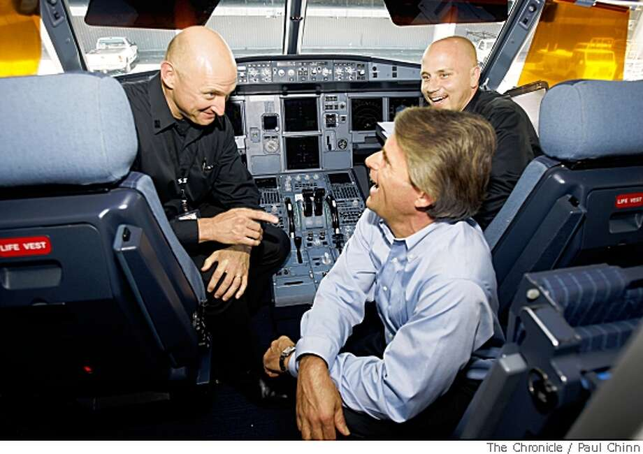 Virgin America Airlines CEO David Cush, lower right, visits with pilots Christian Hix, left, and Henry Biernacki at San Francisco International Airport in San Francisco, Calif., on Friday, May 16, 2008 before Flight 868 departed for San Diego. The start-up airlines is seeking expansion to include flights to Chicago.Photo by Paul Chinn / San Francisco Chronicle Photo: Paul Chinn, Chronicle