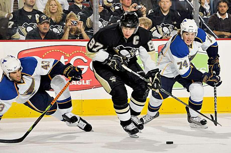 PITTSBURGH - OCTOBER 20: Forward Sidney Crosby #87 of the Pittsburgh Penguins controls the puck as Mike Weaver #43 and TJ Oshie #74 of the St. Louis Blues defend on October 20, 2009 at Mellon Arena in Pittsburgh, Pennsylvania.  (Photo by Jamie Sabau/Getty Images) Photo: Jamie Sabau, Getty Images
