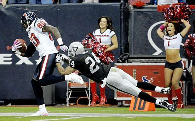 Houston Texans wide receiver Andre Johnson (80) gains yardage and a first down despite the efforts of Oakland Raiders safety Michael Huff (24) during the first quarter of a NFL football game Sunday, Oct. 4, 2009 in Houston. (AP Photo/Dave Einsel) Photo: Dave Einsel, AP