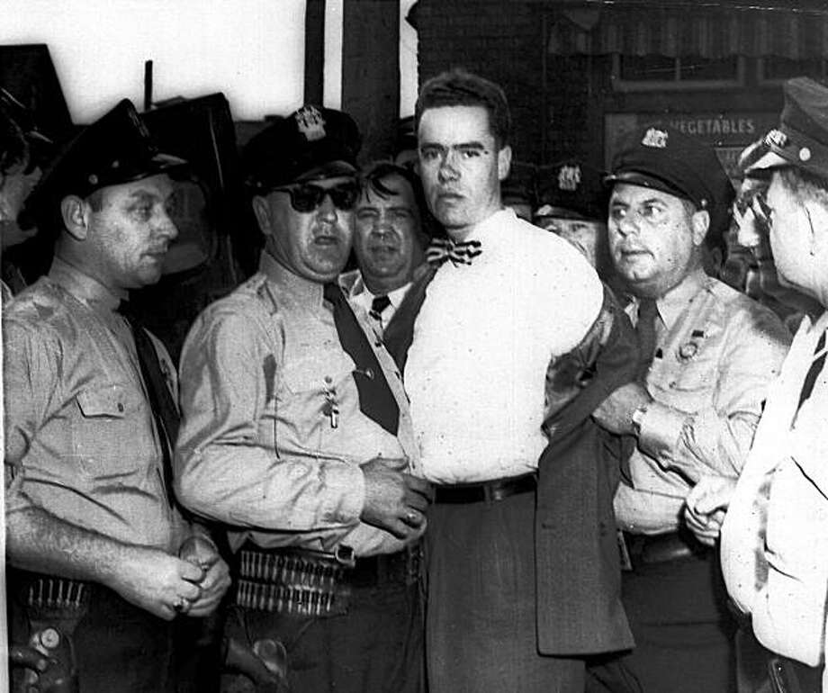 In this Sept. 6, 1949 picture, Howard Unruh, center, is shown with police after his capture in Camden, N.J. Unruh committed a mass murder the day before, gunning down 13 people, in an era when such killings were still rare. On Monday, Oct. 19, 2009, Camden County Prosecutor Warren W. Faulk said Unruh, 88, died at 3:35 p.m. in a Trenton nursing facility after an extended illness. (AP Photo) Photo: AP