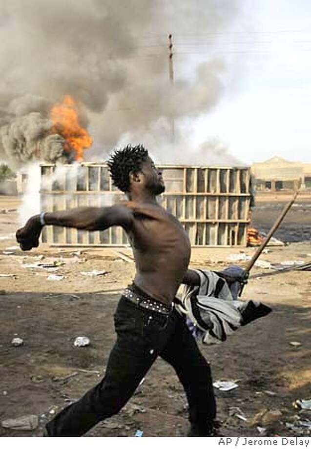 ###Live Caption:A local man throws rocks at South African police in the Reiger Park informal settlement outside Johannesburg Monday May 19, 2008. Mobs rampaged through poor suburbs of Johannesburg in a frenzy of anti-foreigner violence over the weekend, killing at least 12 people, injuring dozens and forcing hundreds to seek refuge at police stations. The attacks capped a week of mounting violence that started in the sprawling township of Alexandra. Angry residents there accused foreigners, many of them Zimbabweans who fled their own country's economic collapse, of taking scarce jobs and housing. . (AP Photo/Jerome Delay)###Caption History:A local man throws rocks at South African police in the Reiger Park informal settlement outside Johannesburg Monday May 19, 2008. Mobs rampaged through poor suburbs of Johannesburg in a frenzy of anti-foreigner violence over the weekend, killing at least 12 people, injuring dozens and forcing hundreds to seek refuge at police stations. The attacks capped a week of mounting violence that started in the sprawling township of Alexandra. Angry residents there accused foreigners, many of them Zimbabweans who fled their own country's economic collapse, of taking scarce jobs and housing. . (AP Photo/Jerome Delay)###Notes:###Special Instructions: Photo: Jerome Delay