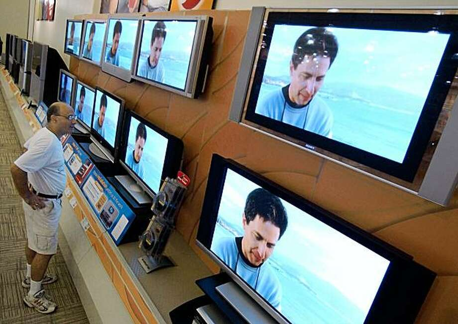 A consumer looks at a wall of plasma screen televisions at a store in Richmond, Virginia. Photo: Steve Helber, AP