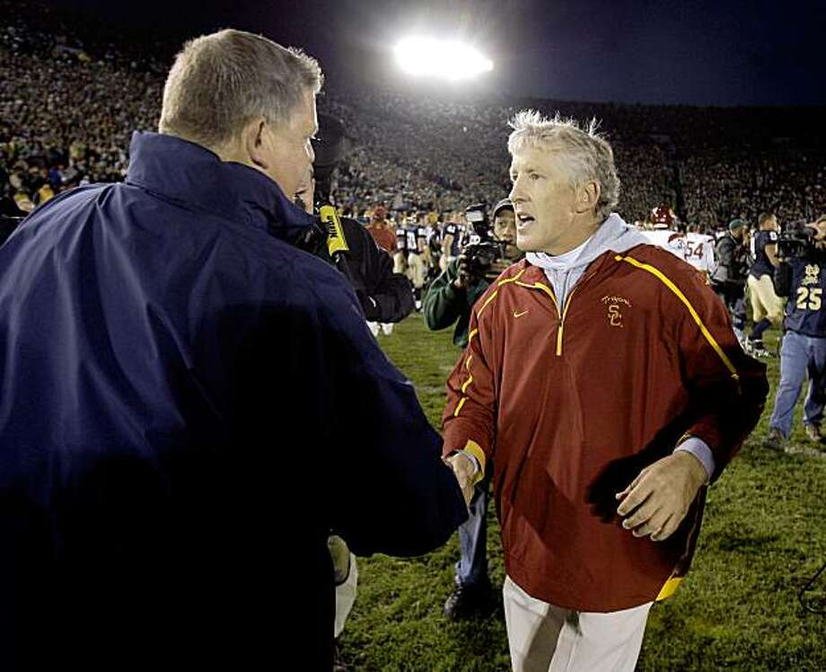 Norte Dame coach Charlie Weis, left,  and Southern California coach Pete Carroll meet following their NCAA college football game in South Bend, Ind., Saturday, Oct. 17, 2009. USC defeated Notre Dame 34-27. (AP Photo/Michael Conroy) Photo: Michael Conroy, AP