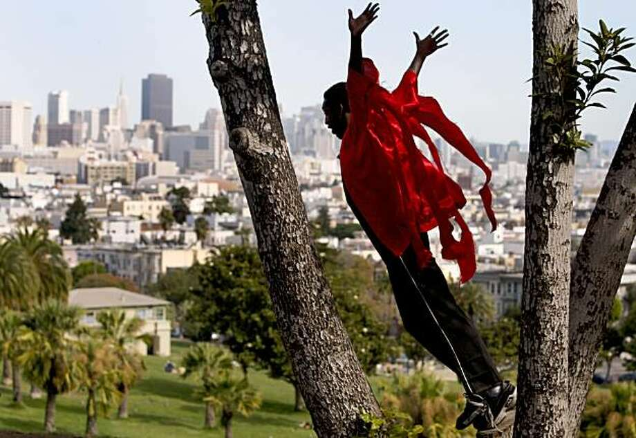 "Antoine Hunter leaps from a tree during a dance as the ""Fire Man"" at the 6th annual Trolley Dances performance in San Francisco, Calif., on Saturday, Oct. 17, 2009. Seven dance companies performed along the Muni J-Church street car line from Dolores Park to Balboa Park. Photo: Paul Chinn, The Chronicle"