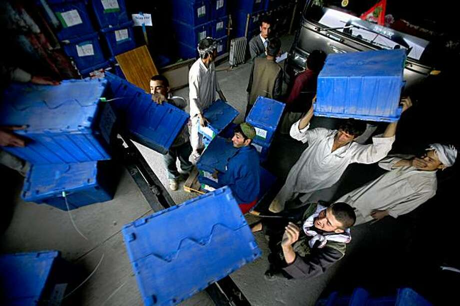 Workers load ballot boxes on to trucks at the Independent Election Commission compound in Kabul, Afghanistan, Thursday, Oct. 22, 2009. The United Nations began delivering ballots and voting kits across Afghanistan Thursday, as full-blown preparations for the Nov. 7 runoff in the insurgency-plagued nation's presidential election got underway. (AP Photo/Altaf Qadri) Photo: Altaf Qadri, AP