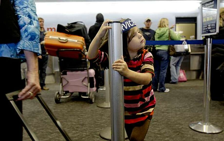 5-year-old Amelia Maguire waits for her dad, Ted Maguire as he tries to get his family of five back to Kansas City as their original flight was cancelled, after working through Midwest, Frontier and United they finally found a flight on United, leaving four hours after their originally scheduled flight.  Flights were delayed at SFO due the storm that rolled through the Bay Area bringing heavy rains on Tuesday October 13, 2009  in San Francisco, Calif. Photo: Michael Macor, The Chronicle
