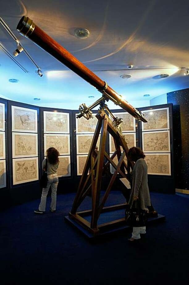 """A 1862 Equatorial telescope, used by Baron Ercole Dembowski to study binary stars, is displayed at the exhibit """"Astrum 2009: Astronomy and Instruments"""" at the Vatican Museum, in Vatican City, Tuesday Oct. 13, 2009.  Rudimentary telescopes, celestial globes and original manuscripts by many astronomical scientists including Dembowski and Galileo are going on view at the Vatican Museums as part of an exhibit marking the U.N. International Year of Astronomy.  The exhibit illustrates the history of astronomy, from a 3rd century A.D. globe of the Zodiac through the increasingly complicated telescopes used to gaze at the stars.  (AP Photo/Pier Paolo Cito) Photo: Pier Paolo Cito, AP"""