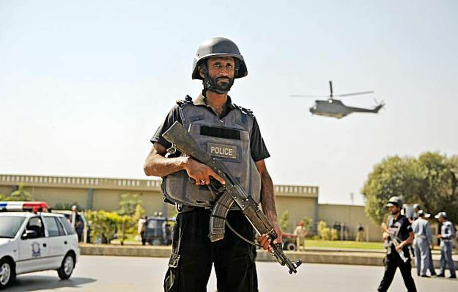 To go with Pakistan-unrest-attacks by Nasir Jaffry (FILES) In a file picture taken on October 10, 2009 Pakistani police commandos take position after an attack on the entrance of army headquarters in the garrison city Rawalpindi. A recent avalanche of attacks killing more than 160 people has opened the flood gates to a widening guerrilla war in Pakistan that the government has no strategy to counter, analysts say on October 16, 2009. AFP PHOTO/Farooq NAEEM (Photo credit should read FAROOQ NAEEM/AFP/Getty Images) Photo: Farooq Naeem, AFP/Getty Images