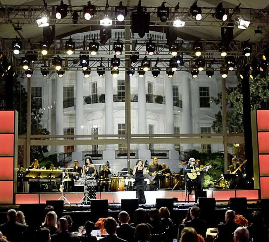 ** ADVANCE FOR TUESDAY, OCT. 20, 2009, AND THEREAFTER ** In this photo taken Oct. 13, 2009, President Barack Obama, center seated facing the stage, watches from left, Shelia E., Gloria Estefan, and Jose Feliciano, perform during the 'Fiesta Latina' on the South Lawn of the White House in Washington. The latest installment of the White House music series was too big for the East Room, so a high-wattage assortment of Latin musicians sent pulsating, can't-help-but-bob-along rhythms tumbling out of a giant tent on the mansion's South Lawn. (AP Photo/Pablo Martinez Monsivais) Photo: Pablo Martinez Monsivais, AP