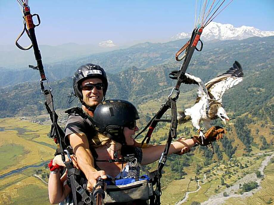 Scott Mason takes the author, Christina Ammon, on a tandem parahawking flight. While Mason pilots the glider and snaps photos, passengers can interact with the raptor in midair. Photo: Scott Mason, Special To The Chronicle