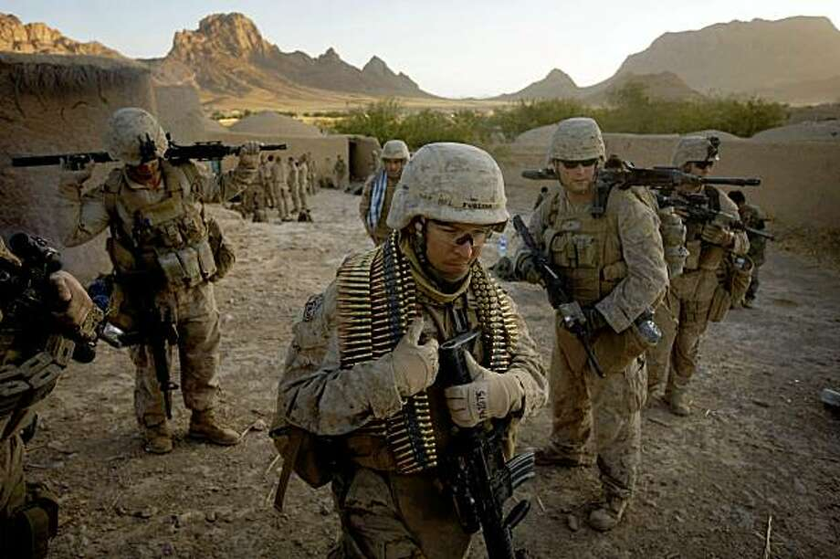 US Marines from Fox Company 2nd Battalion 3rd Marines prepare to set off from their patrol base set up in a house in an Afghan village during day three of Operation Germinate into the restive Bhuji Bhast Pass in Farah Province, southern Afghanistan, on October 9, 2009.  The Bhuji Bhast Pass is effectively a Taliban corridor, mined with IED's from one end to the other, and lined with villages that are hostile to the Western troop presence.  Aboard Marine CH-53 helicopters Fox Company inserted into the pass on the 8th anniversary of the US invasion of Afghanistan in an effort to clear insurgent forces from local villages and improve security for the local Afghan population.  AFP PHOTO/DAVID FURST (Photo credit should read DAVID FURST/AFP/Getty Images) Photo: David Furst, AFP/Getty Images