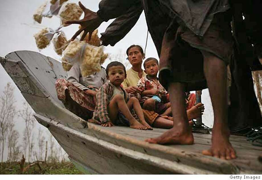 ###Live Caption:MAUBIN, MYANMAR - MAY 18: (ISRAEL OUT) Locals receive food donation May 18, 2008, at the village of Maubin in the Ayeyarwaddy delta, Myanmar. It has been estimated that more than 100,000 people were killed by Cyclone Nargis. International Aid Agencies are continuing efforts to deliver aid into Myanmar in order to assist up to one million people made homeless. (Photo by Getty Images)###Caption History:MAUBIN, MYANMAR - MAY 18: (ISRAEL OUT) Locals receive food donation May 18, 2008, at the village of Maubin in the Ayeyarwaddy delta, Myanmar. It has been estimated that more than 100,000 people were killed by Cyclone Nargis. International Aid Agencies are continuing efforts to deliver aid into Myanmar in order to assist up to one million people made homeless. (Photo by Getty Images)###Notes:MMR: Cyclone Aid Starts To Trickle In To Burma###Special Instructions:(ISRAEL OUT) Photo: Getty Images
