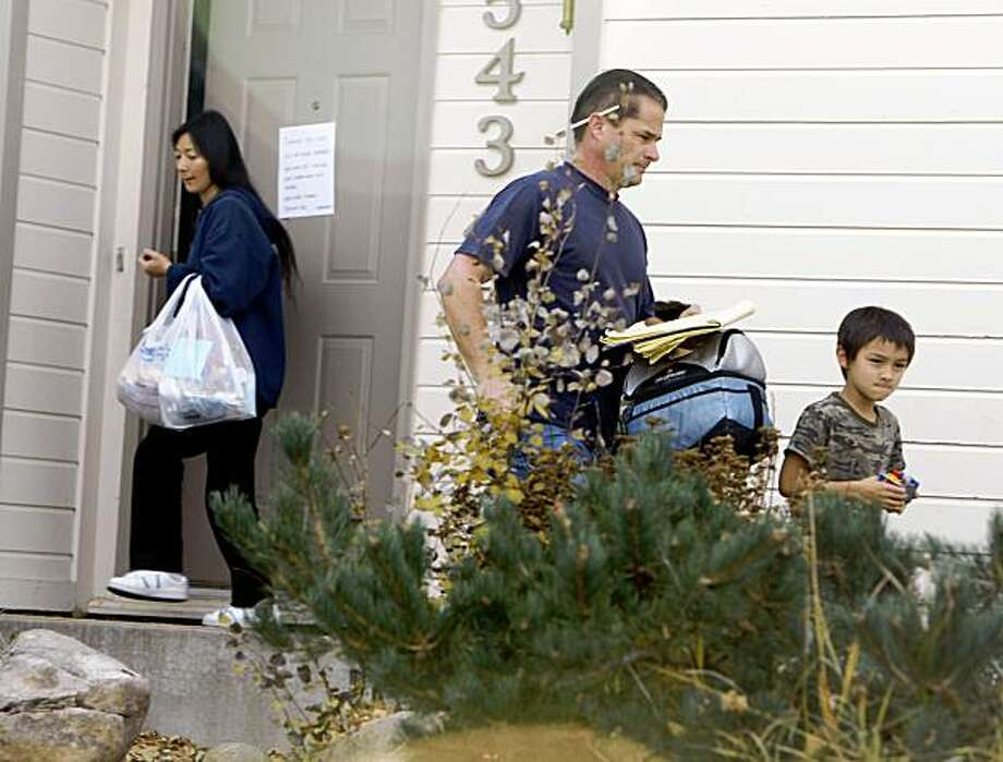 Richard Heene, center, follows his son, Falcon, right, as Mayumi Heene blocks the door as they leave their home in Fort Collins,, Colo., early on Sunday, Oct. 18, 2009. (AP Photo/David Zalubowski) Photo: David Zalubowski, AP