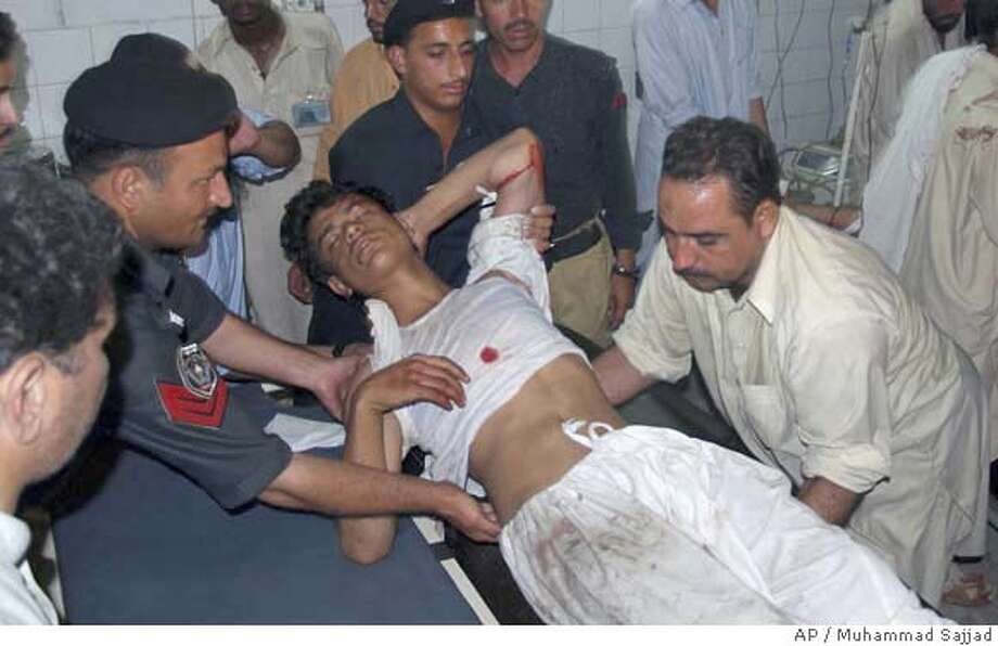 ###Live Caption:An injured victim of Mardan's suicide bombing is carried by police officers and a paramedic for treatment at a local hospital in Peshawar, Pakistan on Sunday May 18, 2008. A suicide bomber attacked a busy market just outside an army base in Pakistan's militancy-plagued northwest Sunday, killing at least 10 people _ including four soldiers _ and wounding 18, officials said. (AP Photo/Muhammad Sajjad)###Caption History:An injured victim of Mardan's suicide bombing is carried by police officers and a paramedic for treatment at a local hospital in Peshawar, Pakistan on Sunday May 18, 2008. A suicide bomber attacked a busy market just outside an army base in Pakistan's militancy-plagued northwest Sunday, killing at least 10 people _ including four soldiers _ and wounding 18, officials said. (AP Photo/Muhammad Sajjad)###Notes:###Special Instructions: Photo: Muhammad Sajjad