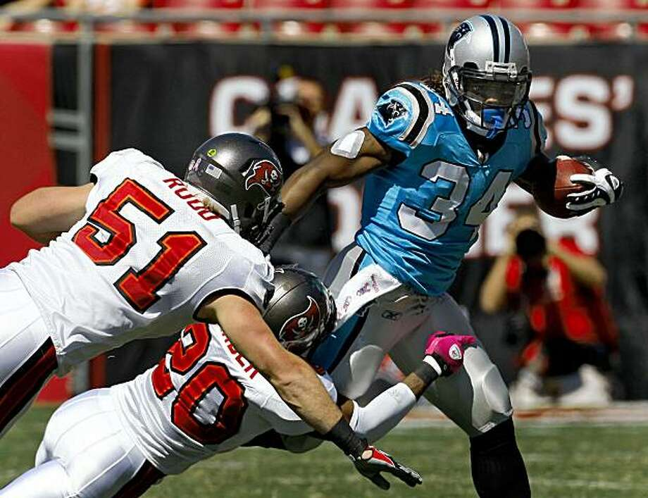 Tampa Bay Buccaneers' Ronde Barber (20) and Barrett Ruud (51) team up to bring down Carolina Panthers running back DeAngelo Williams (34) during a first-quarter run in an NFL football game Sunday, Oct. 18, 2009. (AP Photo/Chris O'Meara) Photo: Chris O'Meara, AP