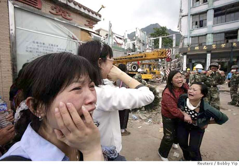 ###Live Caption:Parents cry in front of the rubble of a collapsed high school as they wait for news of their children at the earthquake-hit township of Hanwang in Mianzhu city, northeast of Chengdu in Sichuan province, May 14, 2008. China poured more troops into the earthquake-ravaged province of Sichuan on Wednesday to speed up the search for survivors as time ran out for thousands of people buried under rubble and mud. At least one survivor is seen trapped in the rubble of the school. REUTERS/Bobby Yip (CHINA)###Caption History:Parents cry in front of the rubble of a collapsed high school as they wait for news of their children at the earthquake-hit township of Hanwang in Mianzhu city, northeast of Chengdu in Sichuan province, May 14, 2008. China poured more troops into the earthquake-ravaged province of Sichuan on Wednesday to speed up the search for survivors as time ran out for thousands of people buried under rubble and mud. At least one survivor is seen trapped in the rubble of the school. REUTERS/Bobby Yip (CHINA)###Notes:Parents cry in front of the rubble of a collapsed high school as they wait for news of their children at the earthquake-hit township of Hanwang###Special Instructions: Photo: BOBBY YIP
